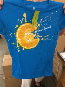 Lady holding up Jamba Juice blue tee