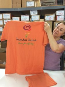 Lady holding up Jamba Juice orange tee